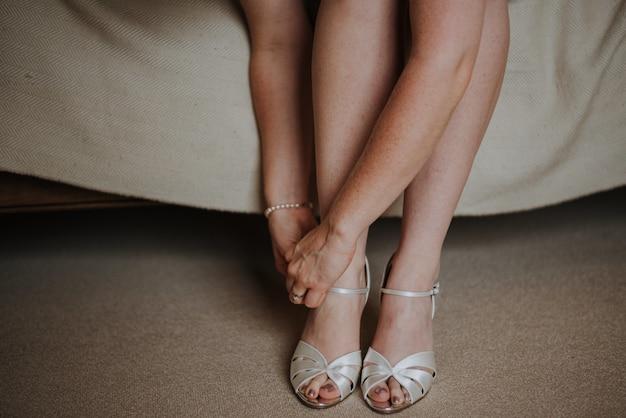 Colpo del primo piano di una femmina che lega le sue scarpe bianche