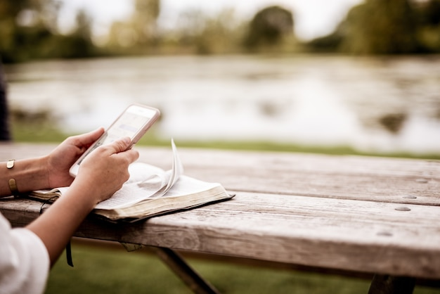 Closeup shot of a female using her smartphone with the bible