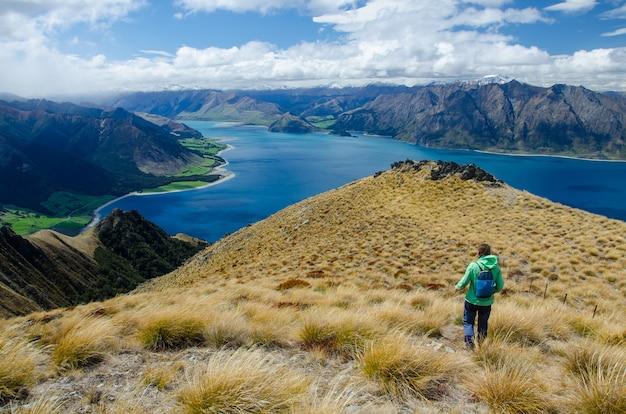 Primo piano di una donna che cammina all'istmus peak e a un lago in nuova zelanda