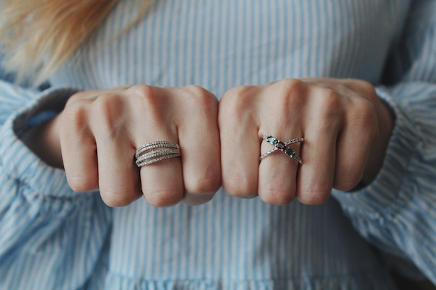 Colpo del primo piano di una donna che indossa bellissimi anelli su entrambe le mani e mostra con i pugni