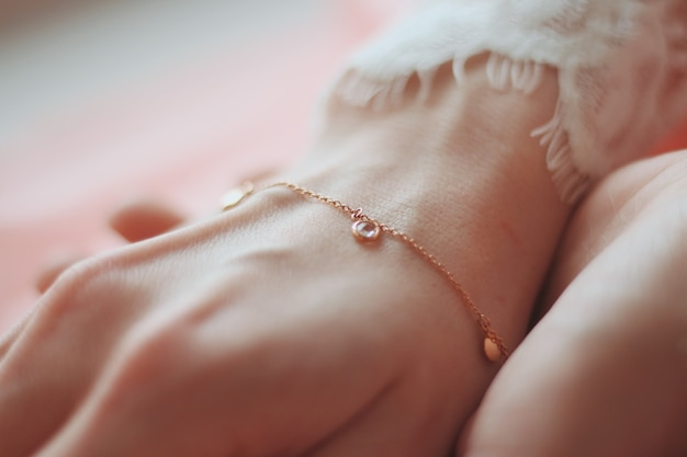 Closeup shot of a female wearing a fashionable bracelet with charm pendants