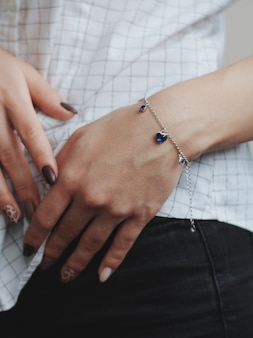 Closeup shot of a female wearing a fashionable silver charm bracelet