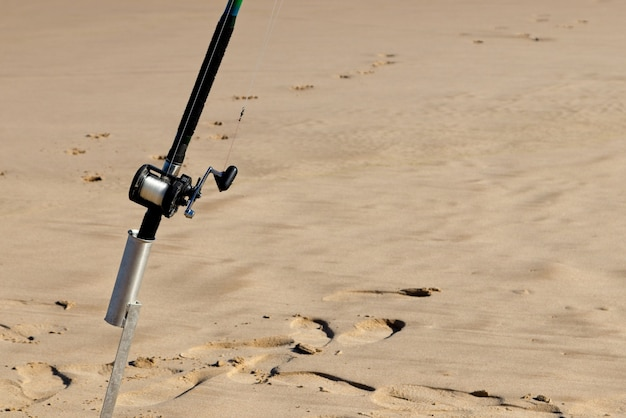 Closeup shot of a fishing pole in a sandy surface