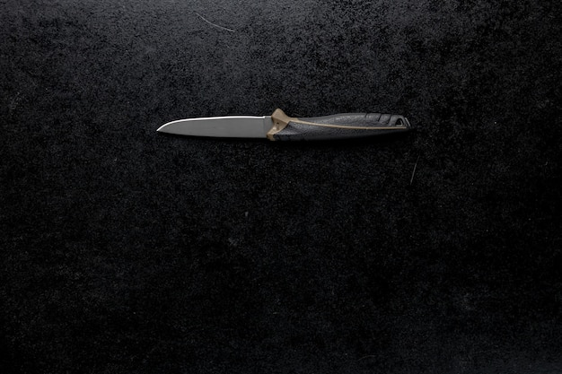 Closeup shot of a fixed sharp knife on a black table