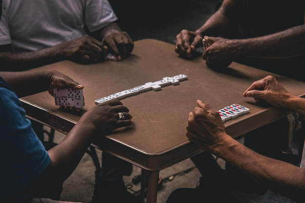 Closeup shot of four african people playing dominoes around a table
