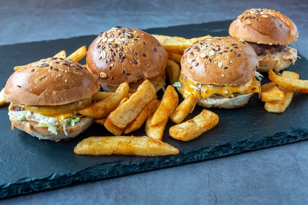Closeup shot of four delicious sliders and a pile of crispy fries on a slate plate
