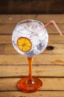 Closeup shot of a fresh cold cocktail with ice cubes and a slice of lemon on a wooden surface