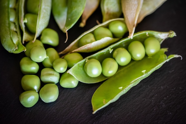 Closeup shot of fresh green pea seeds on black wooden background