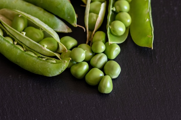Closeup shot of fresh green pea seeds on black wooden table