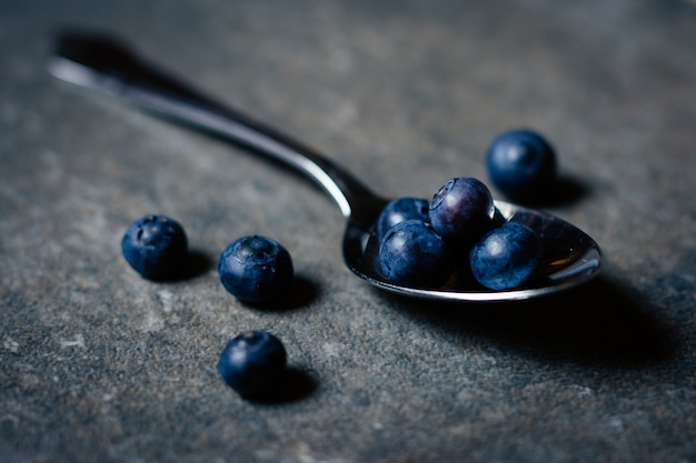 Closeup shot of fresh organic blueberries  silver spoon on wooden table