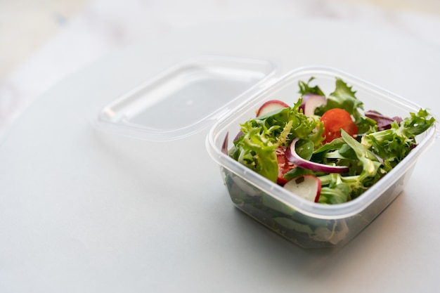 Primo piano di insalata fresca in una scatola di plastica su una superficie bianca