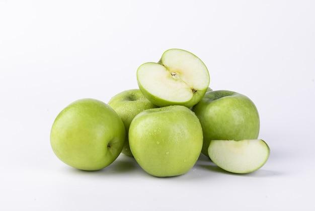 Colpo del primo piano delle mele verdi affettate fresche isolate sulla parete bianca