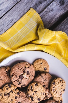 Closeup shot of freshly baked chocolate chip cookies in a white plate on a yellow textile