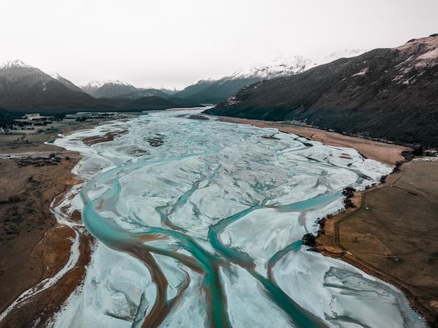 Primo piano di un fiume ghiacciato nelle montagne innevate