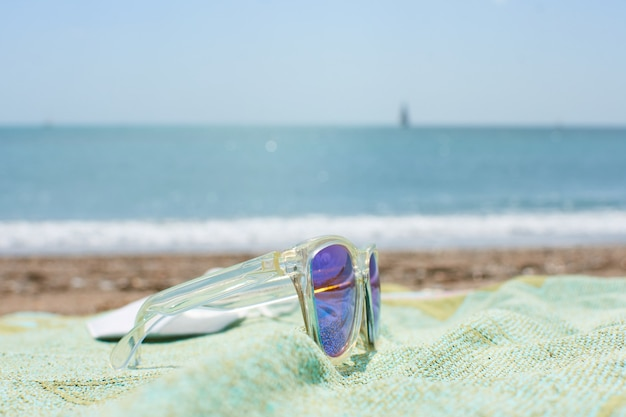 Primo piano di occhiali da sole funky sull'asciugamano da spiaggia su una spiaggia di sabbia