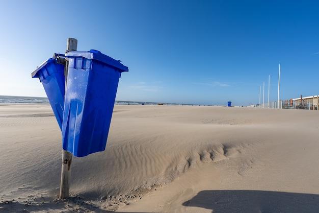 Colpo del primo piano di contenitori di immondizia in spiaggia al tramonto