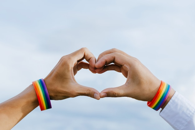 Closeup shot of a gay couple holding hands with a rainbow wristband made hands forming a heart shape