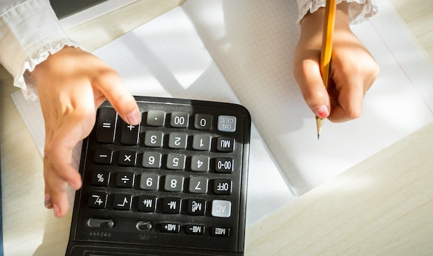 Closeup shot of girl in school uniform solving task with help of calculator