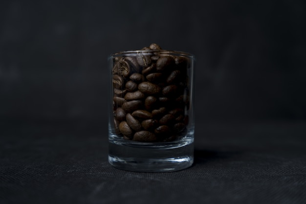 Closeup shot of a glass of coffee beans on a dark surface