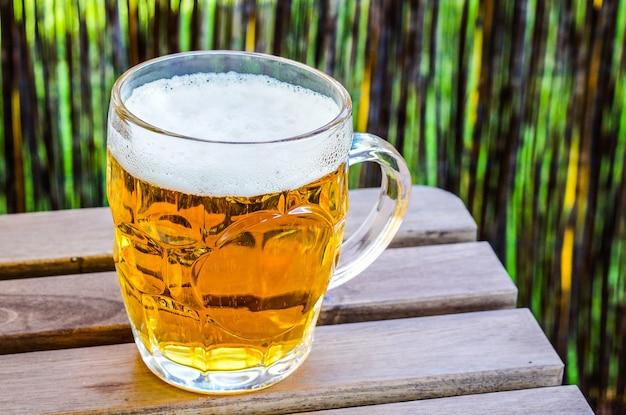 Colpo del primo piano di un bicchiere di birra fredda su una superficie di legno