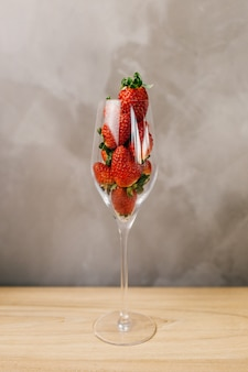 Closeup shot of a glass full of whole strawberries in front of a grey wall
