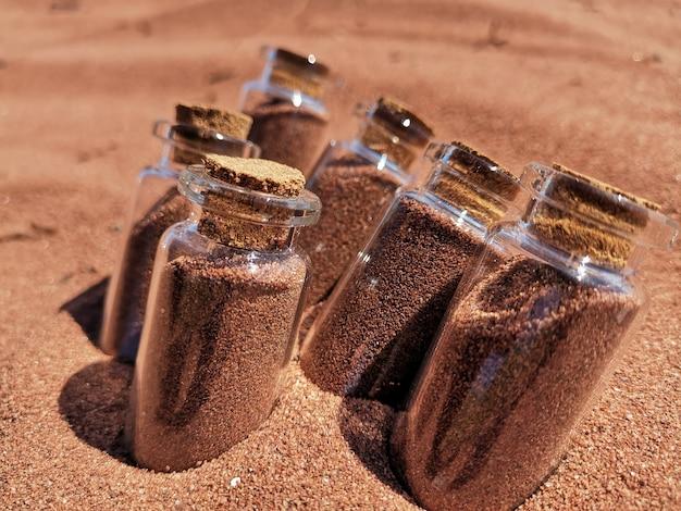 Colpo del primo piano dei barattoli di vetro riempiti di sabbia rossa nella sabbia alla spiaggia