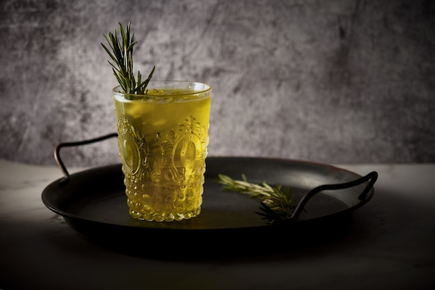 Closeup shot of a glass of yellow drink with rosemary leaves