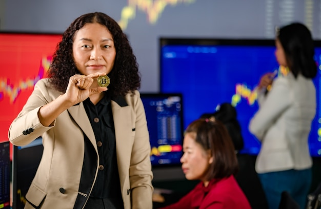 Closeup shot of golden bitcoin electronic token cryptocurrency money in asian businesswoman hand in trade room with investors monitoring market graph chart on computer screen in blurred background.