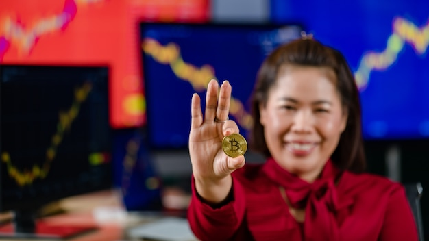 Closeup shot of golden bitcoin electronic token cryptocurrency money in businesswoman investor hand in blurred background with computer monitor graph chart trading buy sell screen financial market.