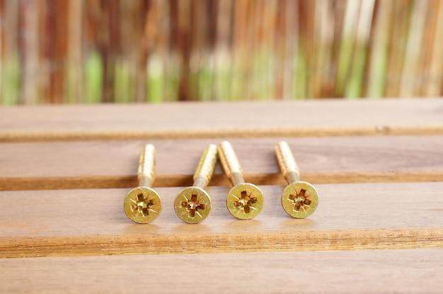 Closeup shot of golden cross screws on a golden table