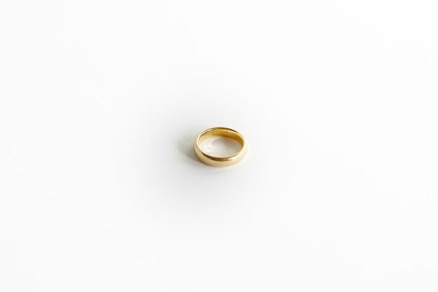 Colpo del primo piano di un anello d'oro isolato su sfondo bianco