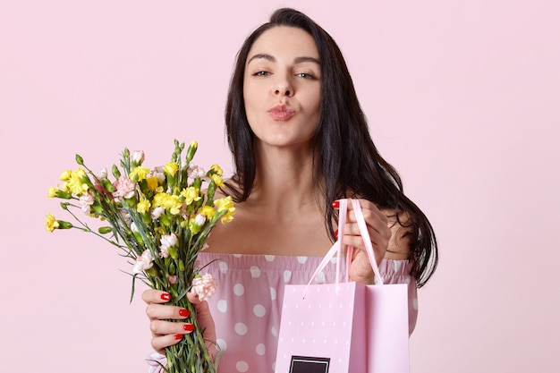 Closeup shot of good looking dark haired young woman keeps lips folded, holds gift bag and flowers, gives present to friend