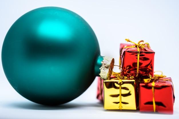 Colpo del primo piano di un ornamento verde dell'albero di natale vicino ai regali colorati