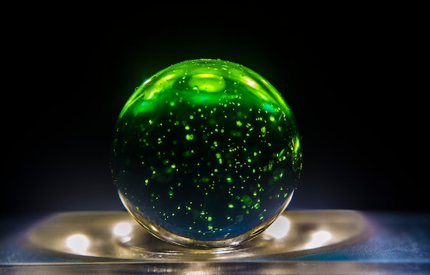 Closeup shot of a green marble on top of a lit surface
