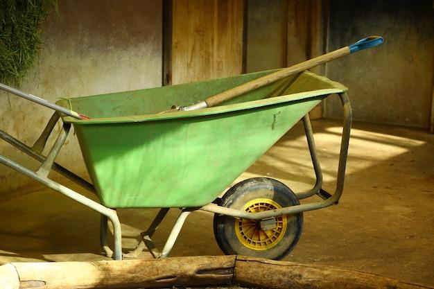 Closeup shot of a green wheelbarrow in a room