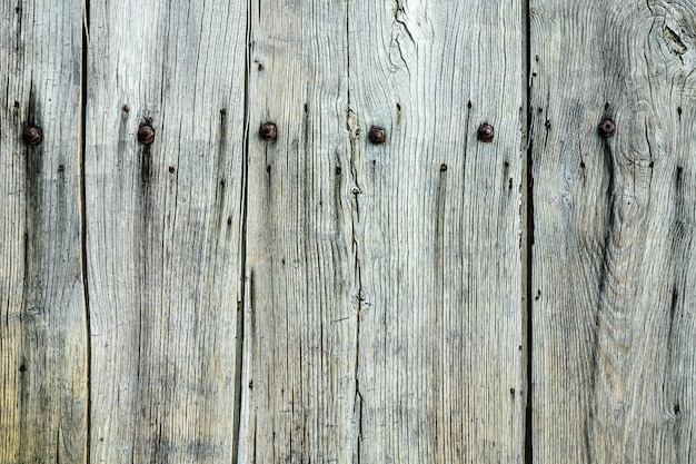 Closeup shot of a grey wooden wall with nails on it