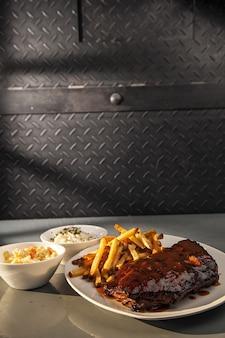 Colpo del primo piano di costolette di maiale alla griglia e patatine fritte con insalata di lato sul tavolo