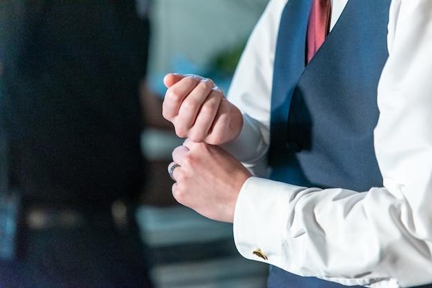Colpo del primo piano dello sposo che regola la sua camicia bianca sul polso