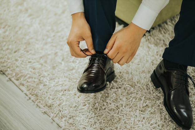 Primo piano dello sposo che fissa i lacci delle scarpe