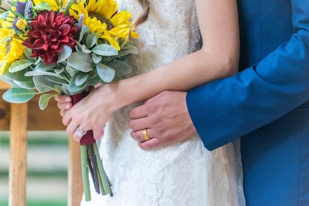 Colpo del primo piano dello sposo che abbraccia la sposa da dietro a una cerimonia di matrimonio