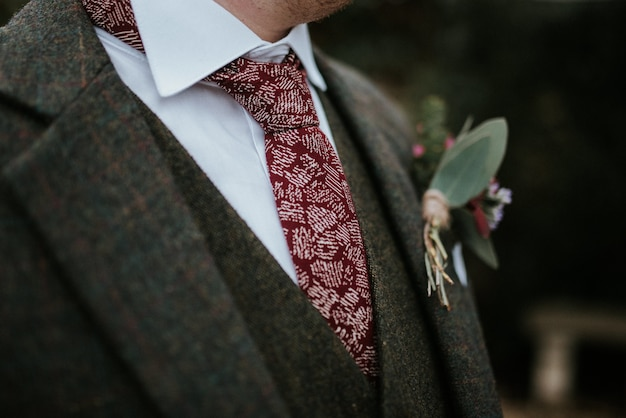 Closeup shot of a groom's suit with flowers and red patterned tie with trees on the background