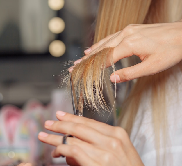 Closeup shot of a hairdresser's hand cutting client's hair after dying