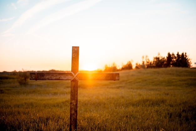 A closeup shot of a handmade wooden cross in the field with the sun shining