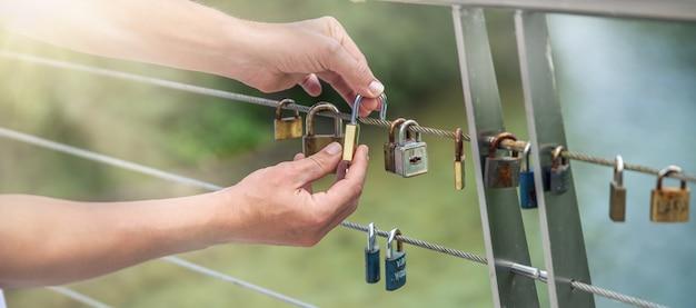 Colpo del primo piano delle mani che appendono le serrature su una corda - concetto di amore