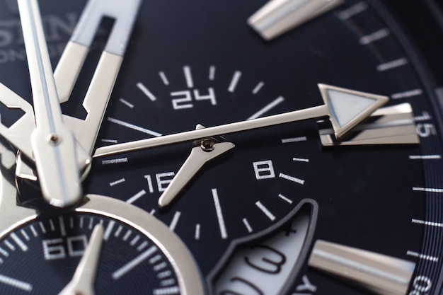 Closeup shot of the hands, numbers and hour marks of a black watch