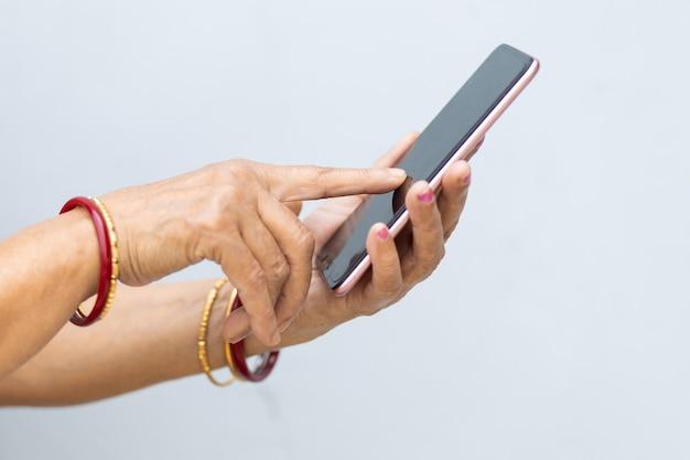 Primo piano delle mani di una persona che manda un sms con il telefono su una sfocatura