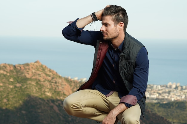 Closeup shot of a handsome male touching his hair in squatting sitting position