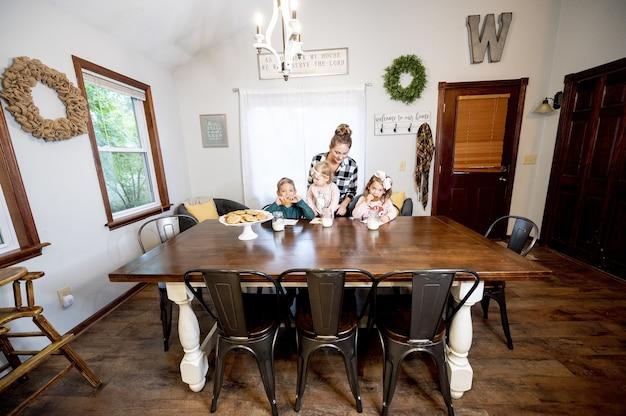 Colpo del primo piano di una famiglia felice che mangia scaglie di cioccolato e che beve latte - concetto di famiglia