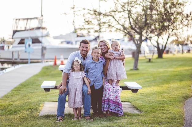 Colpo del primo piano di una famiglia felice in piedi sull'erba vicino al porto - concetto di famiglia