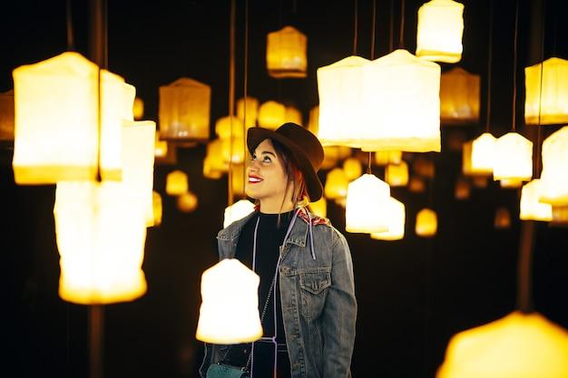 Primo piano di una giovane donna felice in una stanza con molti lampadari luminosi